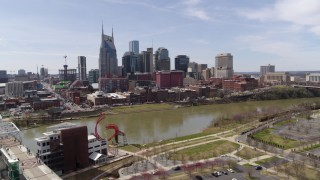 DX0002_117_010 - 5.7K stock footage aerial video orbit city's riverfront skyscrapers across the Cumberland River near the pedestrian bridge, Downtown Nashville, Tennessee
