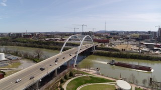 DX0002_117_014 - 5.7K stock footage aerial video of a barge sailing away from a bridge in Nashville, Tennessee