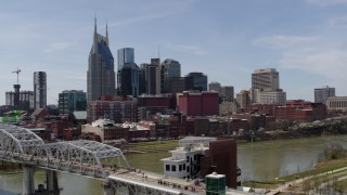 DX0002_117_024 - 5.7K stock footage aerial video ascend by pedestrian bridge, focus on city's skyline, Downtown Nashville, Tennessee
