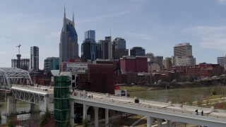 DX0002_117_025 - 5.7K stock footage aerial video descend by pedestrian bridge with view of city's skyline, Downtown Nashville, Tennessee