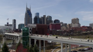 DX0002_117_026 - 5.7K stock footage aerial video ascend by pedestrian bridge with view of city's skyline, Downtown Nashville, Tennessee
