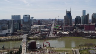 DX0002_117_031 - 5.7K stock footage aerial video descend while focused on busy Broadway across the Cumberland River, Downtown Nashville, Tennessee