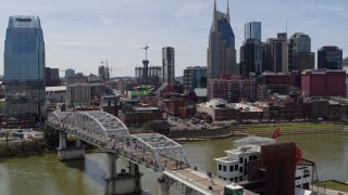 DX0002_117_033 - 5.7K stock footage aerial video descend near pedestrian bridge with view of Broadway across the Cumberland River, Downtown Nashville, Tennessee