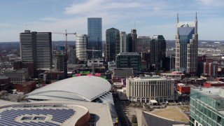 DX0002_117_037 - 5.7K stock footage aerial video passing the city's skyline behind arena and hotel, Downtown Nashville, Tennessee