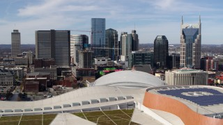 DX0002_117_039 - 5.7K stock footage aerial video ascend near convention center roof for view of city's skyline, Downtown Nashville, Tennessee