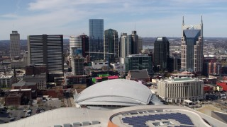 DX0002_117_040 - 5.7K stock footage aerial video passing the city's skyline behind the arena and hotel, Downtown Nashville, Tennessee
