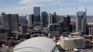 DX0002_117_041 - 5.7K stock footage aerial video flyby and approach city's skyline behind the arena and hotel, Downtown Nashville, Tennessee