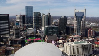 DX0002_117_044 - 5.7K stock footage aerial video of passing by city's skyline, seen from Bridgestone Arena, Downtown Nashville, Tennessee