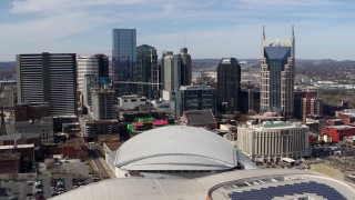 DX0002_117_045 - 5.7K stock footage aerial video of passing the city's skyline, seen behind the arena and hotel, Downtown Nashville, Tennessee