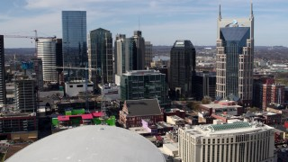 DX0002_117_048 - 5.7K stock footage aerial video of flying away from the city's skyline, Bridgestone Arena, and Hilton hotel, Downtown Nashville, Tennessee