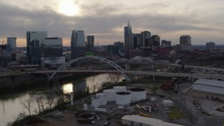 DX0002_119_032 - 5.7K stock footage aerial video of a view of the Cumberland River, bridges, and city skyline at sunset, Downtown Nashville, Tennessee