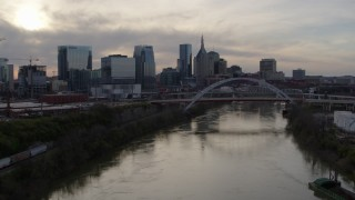 DX0002_119_033 - 5.7K stock footage aerial video descend with view of bridge over river and city skyline at sunset, Downtown Nashville, Tennessee