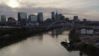 DX0002_119_034 - 5.7K stock footage aerial video follow the river toward the bridge and city skyline at sunset, Downtown Nashville, Tennessee