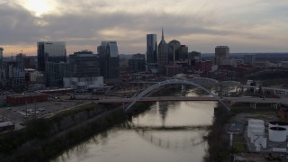 DX0002_119_038 - 5.7K stock footage aerial video the city's skyline and bridges seen while passing the Cumberland River at sunset, Downtown Nashville, Tennessee