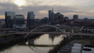 DX0002_119_039 - 5.7K stock footage aerial video the city's skyline while descending past bridges over the Cumberland River at sunset, Downtown Nashville, Tennessee