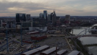 DX0002_119_041 - 5.7K stock footage aerial video reverse view of skyline before passing bridge and Cumberland River at sunset, Downtown Nashville, Tennessee