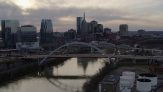DX0002_119_042 - 5.7K stock footage aerial video of the city skyline by bridges and Cumberland River at sunset, Downtown Nashville, Tennessee