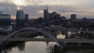 DX0002_119_045 - 5.7K stock footage aerial video ascend past bridge on Cumberland River at sunset, skyline in background, Downtown Nashville, Tennessee