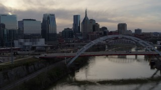 DX0002_119_047 - 5.7K stock footage aerial video the city skyline behind a bridge on Cumberland River at sunset, Downtown Nashville, Tennessee