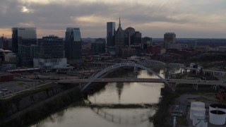 DX0002_119_048 - 5.7K stock footage aerial video fly away from and past city skyline behind a bridge on Cumberland River at sunset, Downtown Nashville, Tennessee