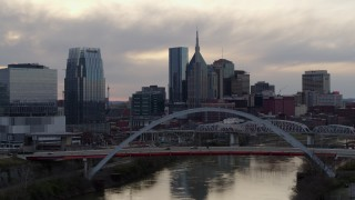 DX0002_120_001 - 5.7K stock footage aerial video city skyline seen while passing bridge on Cumberland River at sunset, Downtown Nashville, Tennessee