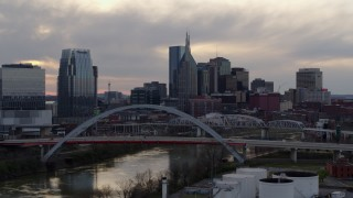 DX0002_120_002 - 5.7K stock footage aerial video city skyline seen while flying by bridge on Cumberland River at sunset, Downtown Nashville, Tennessee