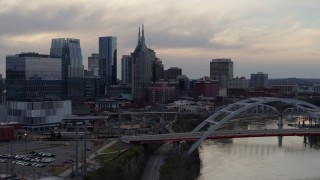 DX0002_120_003 - 5.7K stock footage aerial video riverfront skyline seen while passing bridge on Cumberland River at sunset, Downtown Nashville, Tennessee