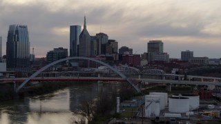 DX0002_120_004 - 5.7K stock footage aerial video flying by riverfront skyline, bridge, and Cumberland River at sunset, Downtown Nashville, Tennessee