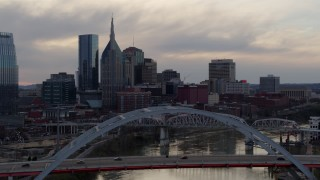 DX0002_120_005 - 5.7K stock footage aerial video approach riverfront skyline, ascend over bridge and Cumberland River at sunset, Downtown Nashville, Tennessee