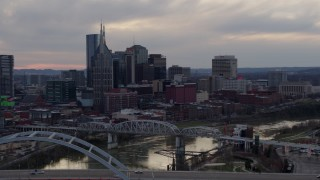 DX0002_120_006 - 5.7K stock footage aerial video flying by and away from riverfront skyline, bridges, and Cumberland River at sunset, Downtown Nashville, Tennessee