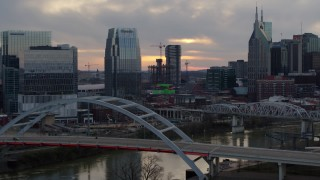 DX0002_120_014 - 5.7K stock footage aerial video focus on a tall skyscraper while passing a bridge on the river at sunset, Downtown Nashville, Tennessee