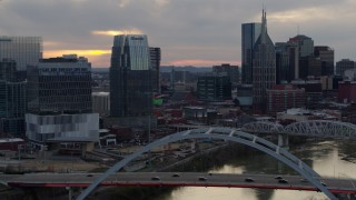 DX0002_120_015 - 5.7K stock footage aerial video focus on a tall skyscraper while flying by a bridge on the river at sunset, Downtown Nashville, Tennessee