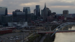 DX0002_120_019 - 5.7K stock footage aerial video approach riverfront skyscrapers by the Cumberland River at sunset, Downtown Nashville, Tennessee