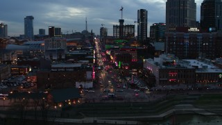 DX0002_120_030 - 5.7K stock footage aerial video of riverfront buildings, cars on Broadway at twilight during ascent, Downtown Nashville, Tennessee