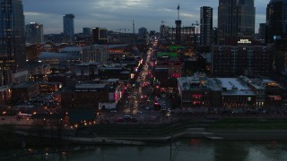 DX0002_120_031 - 5.7K stock footage aerial video reverse view of riverfront buildings, cars on Broadway at twilight, Downtown Nashville, Tennessee