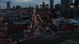 DX0002_120_032 - 5.7K stock footage aerial video flying toward traffic and pedestrians on Broadway at twilight, Downtown Nashville, Tennessee