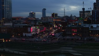 DX0002_120_033 - 5.7K stock footage aerial video descend and flyby traffic and riverfront buildings on Broadway at twilight, Downtown Nashville, Tennessee