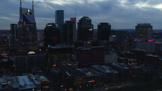 DX0002_120_035 - 5.7K stock footage aerial video ascend while flying by tall skyscrapers near AT&T Building at twilight, Downtown Nashville, Tennessee