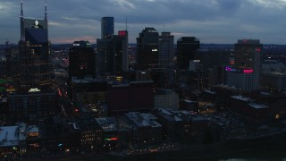 DX0002_120_036 - 5.7K stock footage aerial video flying by the AT&T Building and tall skyscrapers at twilight, Downtown Nashville, Tennessee