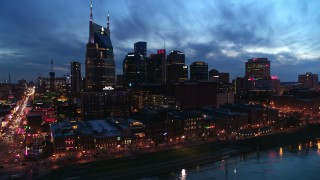DX0002_121_001 - 5.7K stock footage aerial video of flying by the city's skyline at twilight and reveal Broadway, Downtown Nashville, Tennessee