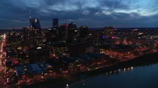 DX0002_121_004 - 5.7K stock footage aerial video of crossing the river toward the city's skyline at twilight, Downtown Nashville, Tennessee