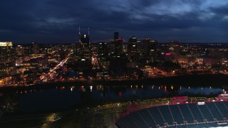 DX0002_121_010 - 5.7K stock footage aerial video approach the city's skyline and river from stadium at twilight, Downtown Nashville, Tennessee
