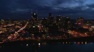 DX0002_121_013 - 5.7K stock footage aerial video flying away from the AT&T Building and skyline at twilight, reveal the river, Downtown Nashville, Tennessee