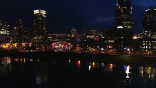 DX0002_121_022 - 5.7K stock footage aerial video approach the end of Broadway with traffic at twilight, descend by the river in Downtown Nashville, Tennessee