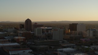 DX0002_122_032 - 5.7K stock footage aerial video of a reverse view of high-rise office buildings at sunset, Downtown Albuquerque, New Mexico