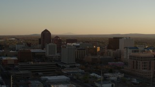 DX0002_122_034 - 5.7K stock footage aerial video fly away from high-rise office buildings at sunset and ascend past Downtown Albuquerque, New Mexico