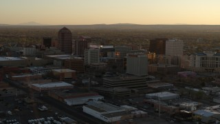 DX0002_122_035 - 5.7K stock footage aerial video of descending past high-rise office buildings at sunset, Downtown Albuquerque, New Mexico