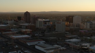 DX0002_122_036 - 5.7K stock footage aerial video of slowly flying by high-rise office buildings at sunset, Downtown Albuquerque, New Mexico