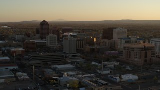 DX0002_122_037 - 5.7K stock footage aerial video of slowly flying away from high-rise office buildings at sunset, Downtown Albuquerque, New Mexico