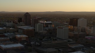 DX0002_122_039 - 5.7K stock footage aerial video of slowly flying toward high-rise office buildings at sunset, Downtown Albuquerque, New Mexico